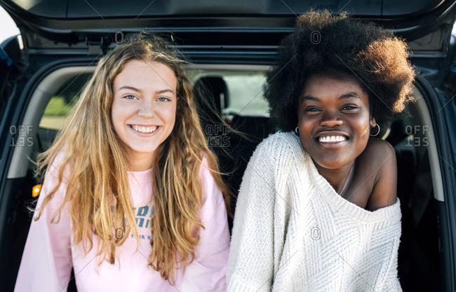 Portrait of two best friends sitting in a car