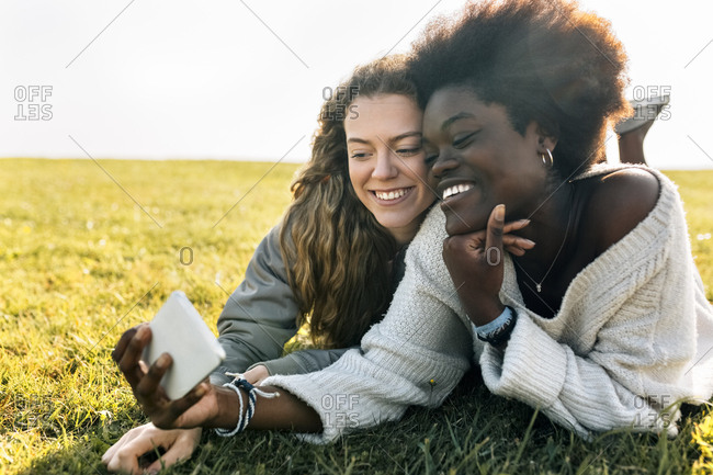 Two best friends lying in grass with cell phone