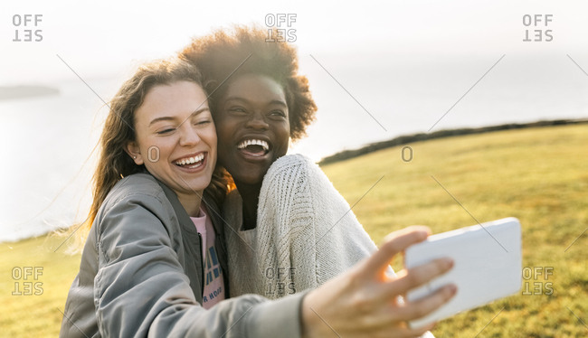 Two happy best friends making a selfie at the coast