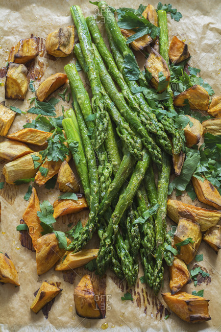 Baked green asparagus- sweet potatoes and flat leaf parsley on baking paper