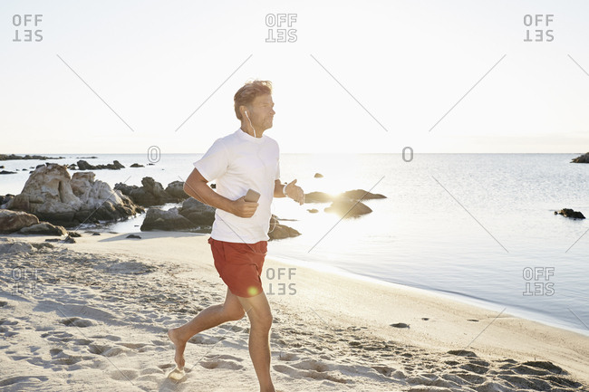 Mature man jogging on the beach while listening music with smartphone and earphones