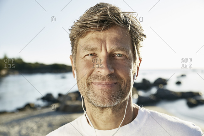 Portrait of confident mature man with earphones on the beach