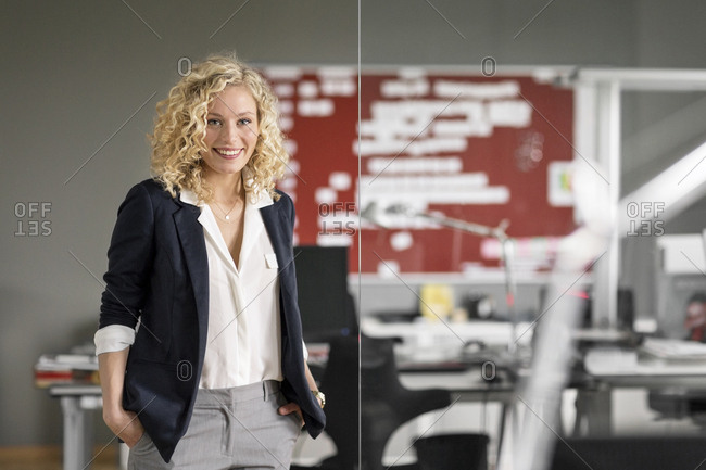 Dynamic businesswoman standing in office- smiling