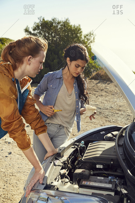 Two young women checking their car standing at the roadside