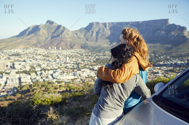 South Africa- Cape Town- Signal Hill- two young women leaning against car overlooking the city