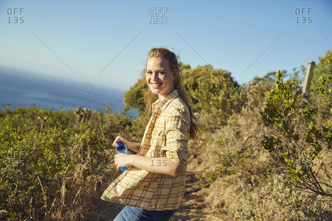 South Africa- Cape Town- Signal Hill- smiling young woman hiking at the coast