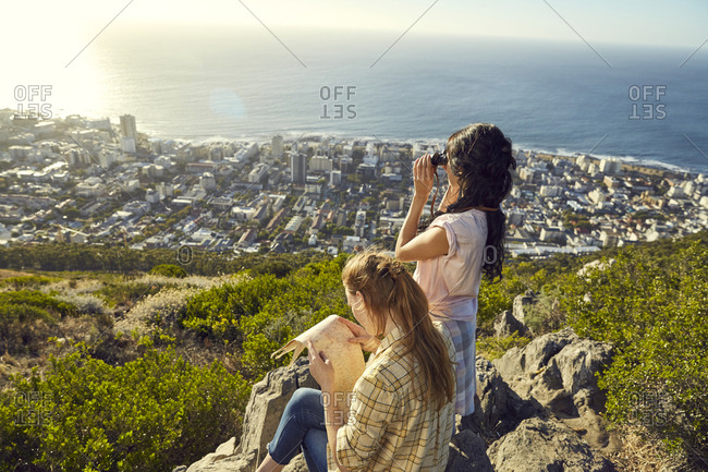 South Africa- Cape Town- Signal Hill- two young women with map and binoculars overlooking the city and the sea