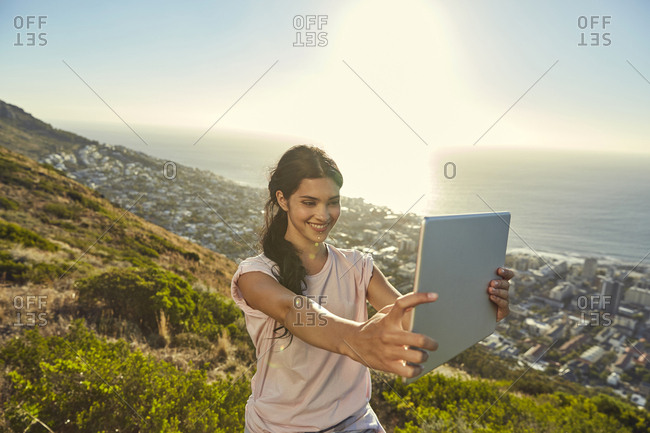 South Africa- Cape Town- Signal Hill- young woman above the city taking a selfie with tablet