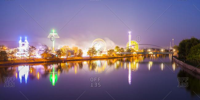 Germany- Stuttgart- lighted Cannstatter Wasen fairground with Neckar River in the foreground