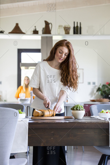 Woman cutting bread for dinner party
