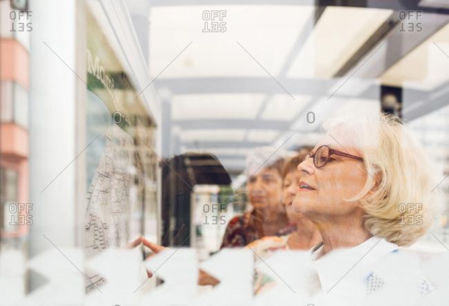 Three women looking at public transportation map