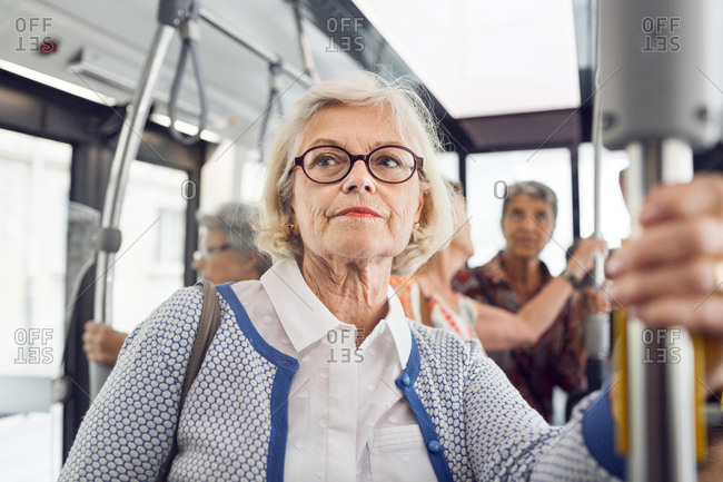 Senior woman holding handrail in bus
