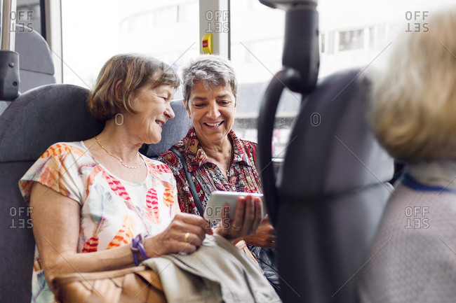Two smiling women looking at mobile phone in bus