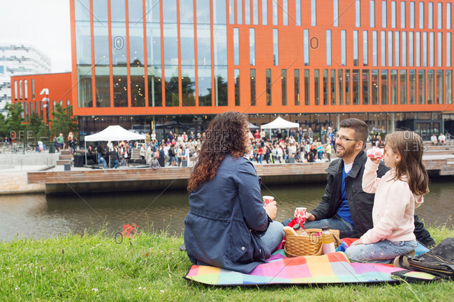 Parents with daughter (4-5) enjoying picnic with concert in background