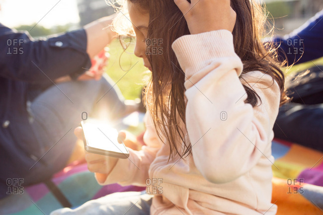 Parents with daughter (4-5) at picnic in town, daughter using smart phone