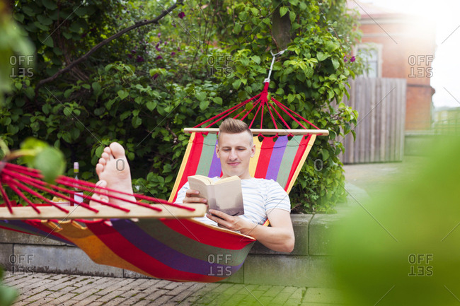 Man reading book on hammock