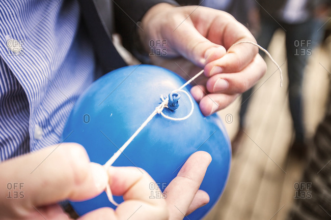 Man tying knot on balloon, close-up