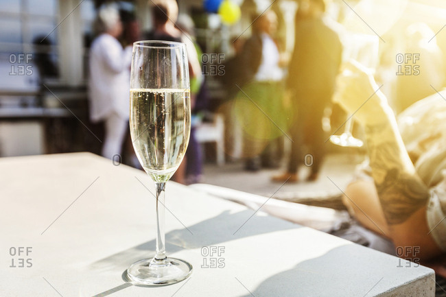 Close-up of glass of champagne on table, woman drinking champagne in background