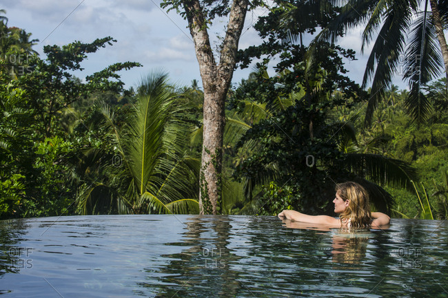 Woman enjoying an overflowing pool above a valley in the Kamandalu Ubud resort