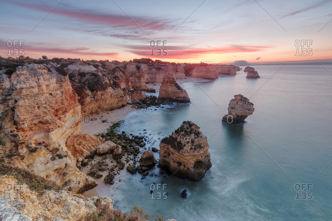 Sunrise on cliffs framed by turquoise water of the ocean Praia da Marinha Caramujeira Lagoa Municipality Algarve Portugal Europe