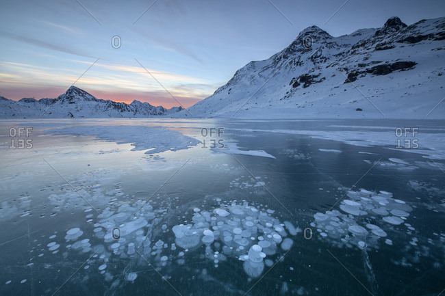 Ice bubbles frame the snowy peaks reflected in Lago Bianco Bernina Pass canton of Graub�_nden Engadine Switzerland Europe