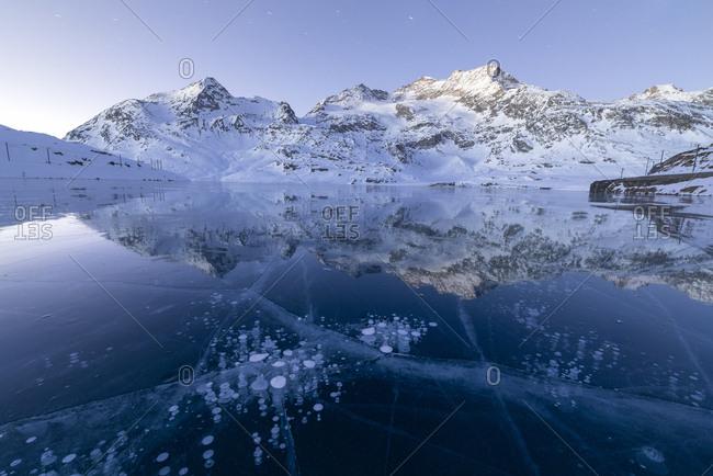 Ice bubbles frame the snowy peaks reflected in Lago Bianco Bernina Pass canton of Graub�_nden Engadine Switzerland Europe