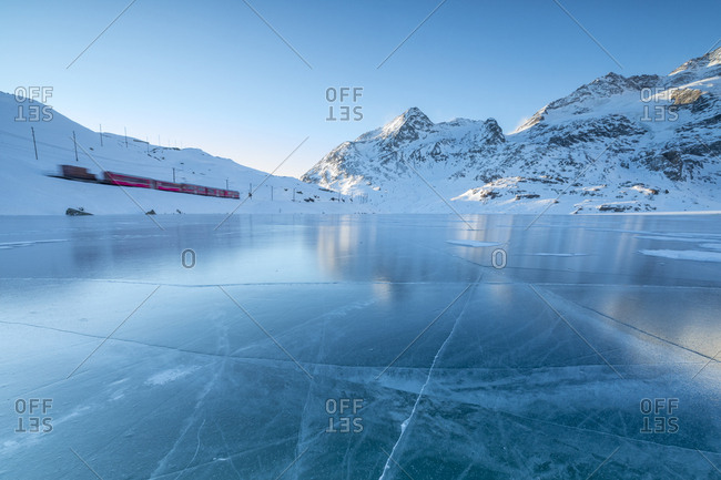 The Bernina Express train runs beside the frozen Lago Bianco Bernina Pass canton of Graub�_nden Engadine Switzerland Europe