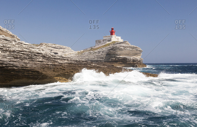 Waves of the turquoise sea crashing on the granite white cliffs and lighthouse Lavezzi Islands Bonifacio Corsica France Europe