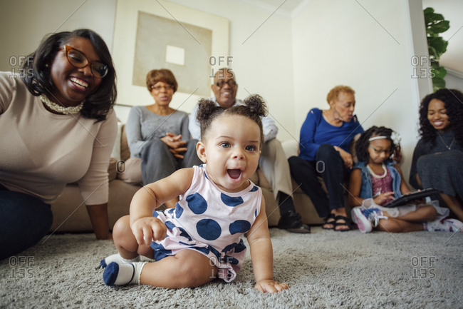 Cute baby girl with multi generational family in living room at home