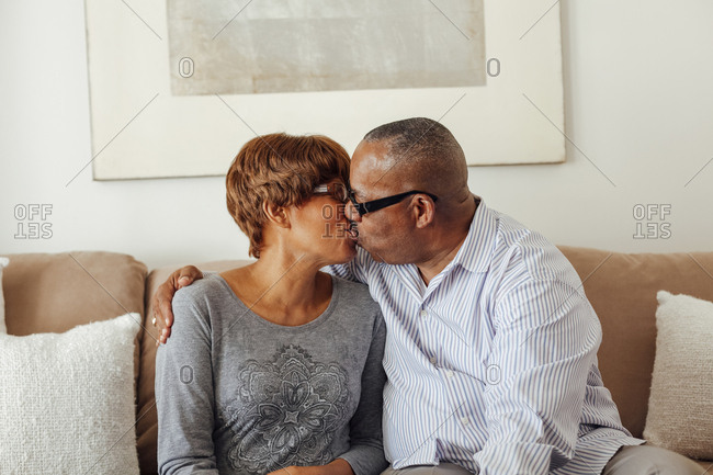 Romantic senior couple kissing on sofa in living room at home