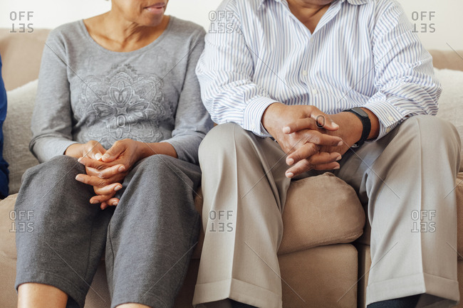 Midsection of senior couple with hands clasped sitting on sofa at home