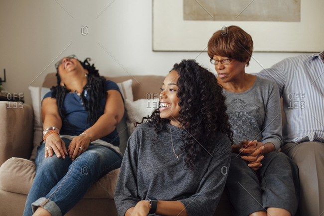 Smiling mid adult woman with family sitting on sofa in living room at home