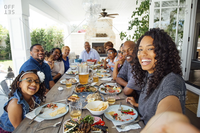 Smiling mid adult woman taking selfie with family during lunch at table on patio
