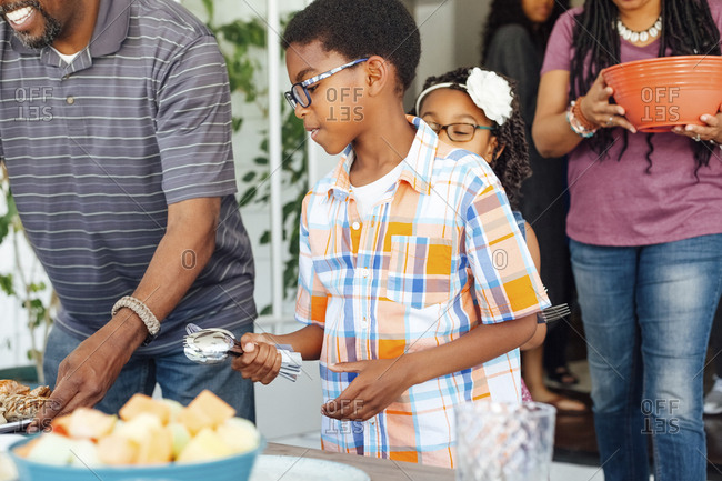Boy holding spoons while family arranging food during lunch at patio