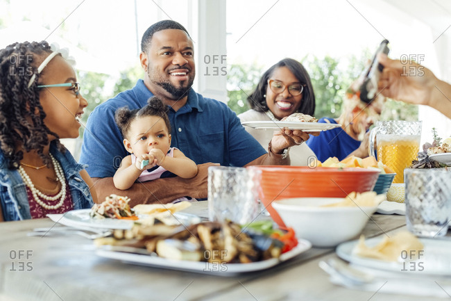 Mid adult man holding baby girl and plate while having lunch with family at patio