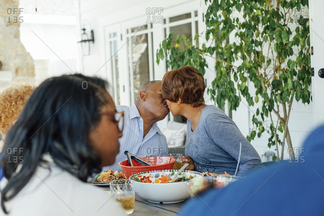 Senior couple kissing while having lunch with family at table on patio