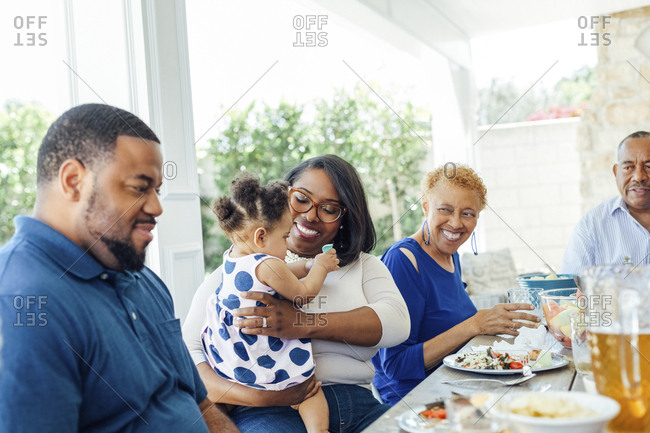 Happy mother holding baby girl while having lunch with family on patio