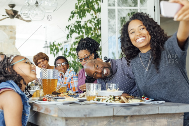 Happy woman taking selfie with family while having lunch on patio