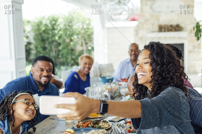 Smiling mid adult woman taking selfie with family at table during lunch