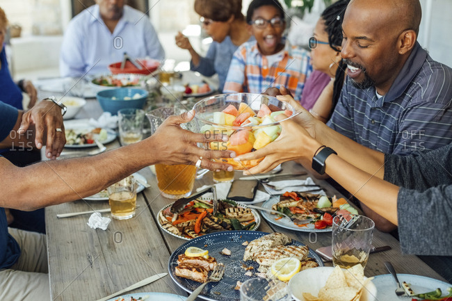Family passing bowl of fruit salad while having lunch at table on patio