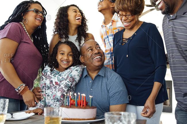 Happy senior man celebrating his birthday with family at patio