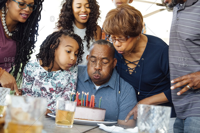 Senior man with family blowing out birthday candles on cake at patio
