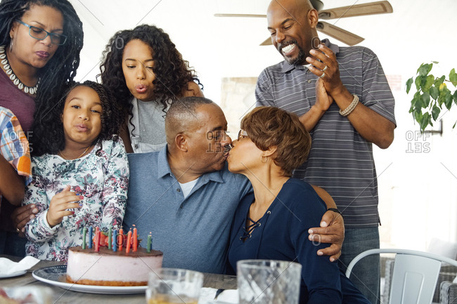 Senior couple kissing while celebrating birthday party with family at patio