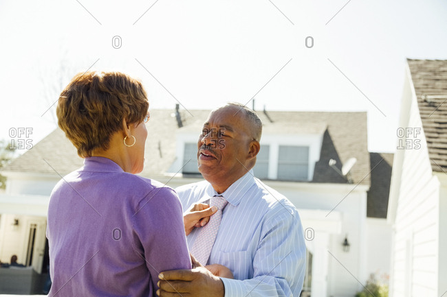Senior woman adjusting man's tie outside home