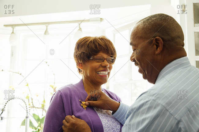 Happy senior man adjusting brooch on woman's jacket at home