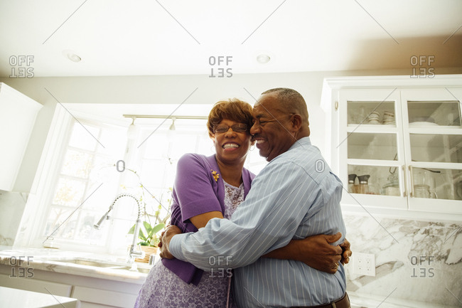Happy senior couple embracing in kitchen at home
