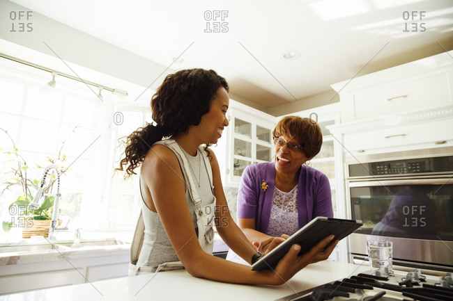 Senior woman talking with daughter holding digital tablet at counter in kitchen