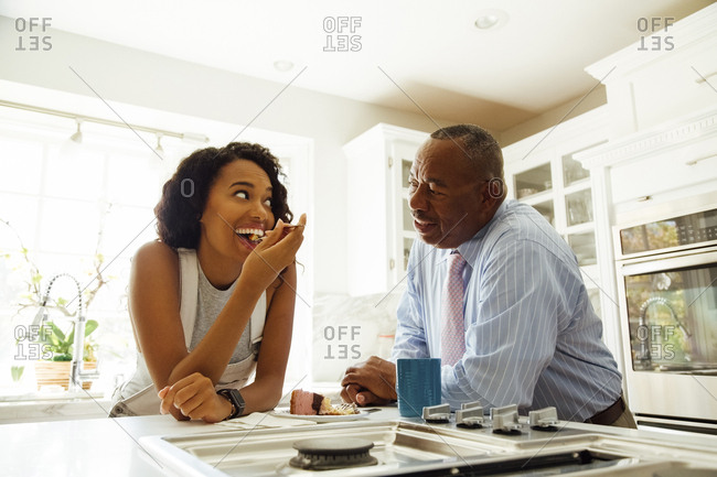Senior man talking to daughter having dessert at counter in kitchen