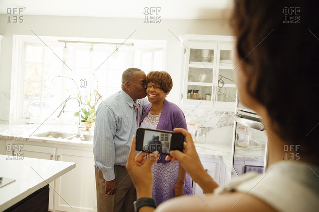 Woman photographing father kissing mother through smartphone in kitchen