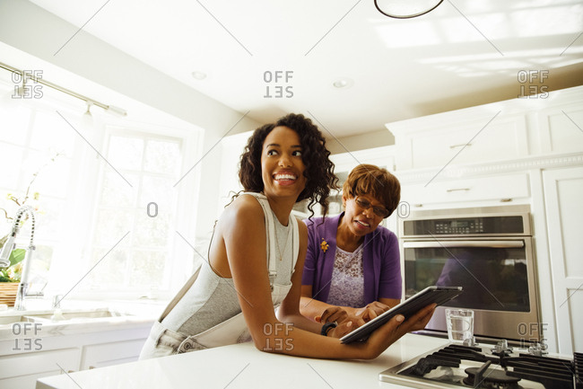 Smiling mid adult woman with digital tablet standing by mother in kitchen